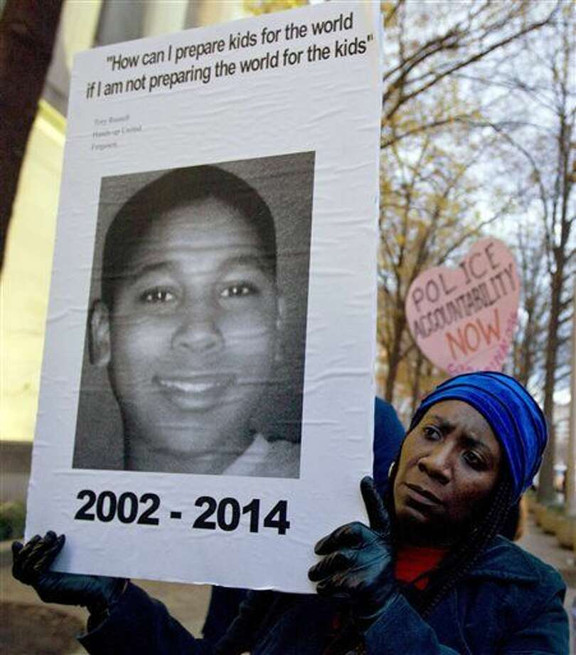 In this Dec. 1, 2014 file photo, Tomiko Shine holds up a picture of Tamir Rice, the 12 year old boy fatally shot by a rookie police officer in Cleveland, Ohio, on Nov. 22, during a protest in Washington, D.C. Cuyahoga County prosecutor Tim McGinty said Monday, Dec. 28, 2015, that a grand jury declined to indict the police officer, Timothy Loehmann, in the killing of Rice, a black youngster shot while holding with what turned out to be a pellet gun. (AP Photo/Jose Luis Magana)