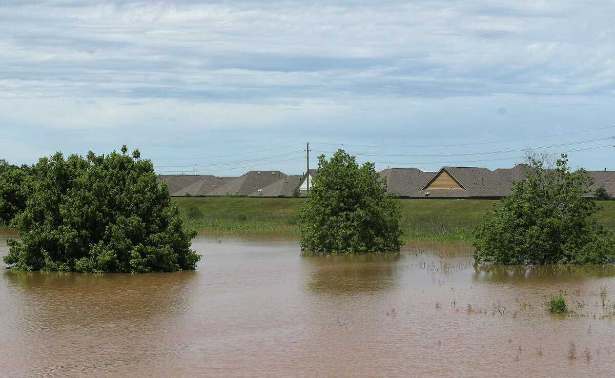 A levy stays put between the Brazos River and homes in Sugarland, Texas on Wednesday, April 20, 2016, in Richmond.