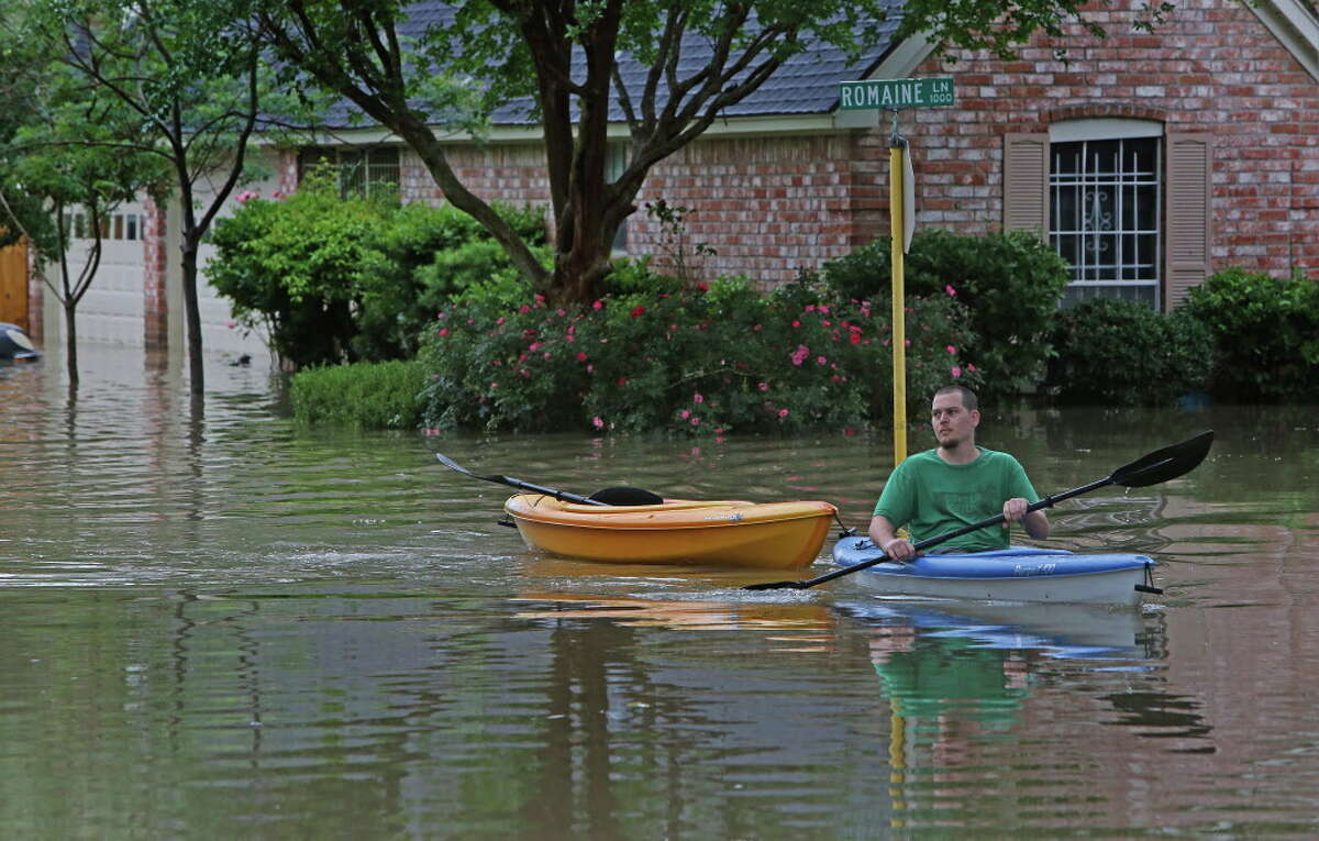 Residents use small boats to deliver goods to neighbors and take them out of their homes near Nanes and Baltic Wednesday, April 20, 2016, in Houston.