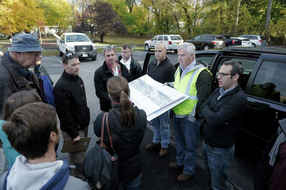 James Flynn, second from right, a project manager with Kinder Morgan, holds a map showing the company's gas pipelines for Federal Energy Regulatory Commission staff and representatives from the Town of Bethlehem on Thursday, Oct. 30, 2014, in Bethlehem, N.Y.  Kinder Morgan is proposing to add a third pipe to a portion of the Tennessee Gas Pipeline.  (Paul Buckowski / Times Union) Photo: Paul Buckowski / 00029137A