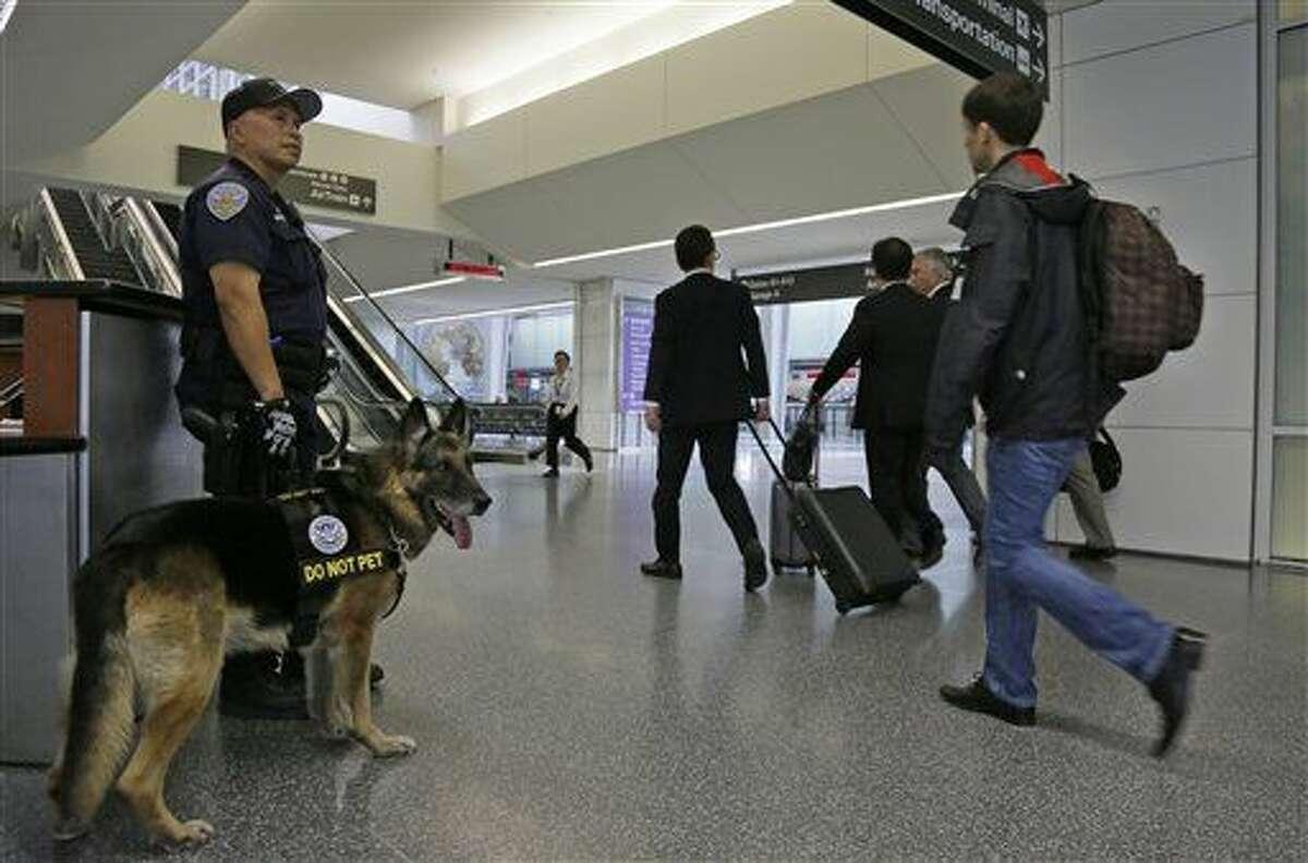 El agente policial Dennis Martínez y su perro Denny vigilan el ingreso al aeropuerto internacional de San Francisco el martes 22 de marzo del 2016. La gente se está acostumbrando a convivir con el miedo tras un nuevo ataque terrorista en el que fallecieorn decenas de personas en Bégica. (AP Photo/Eric Risberg)