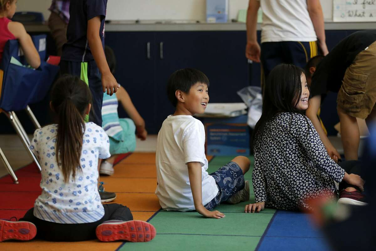 Darren Chao (center) and Jennifer Zhu (right) sit in a 4th grade classroom at the Chinese Immersion School at De Avila in San Francisco, California, on Wednesday, Sept. 9, 2015.