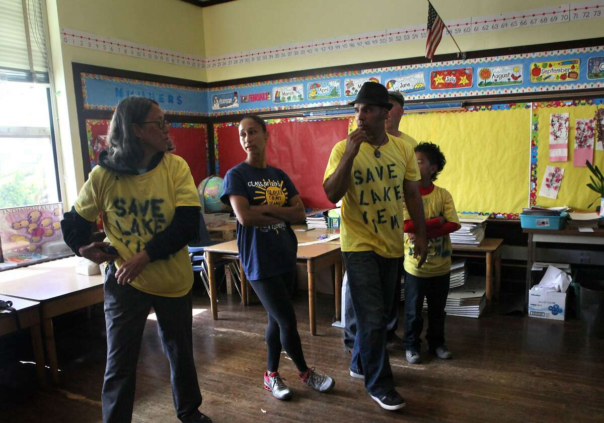 Left to right--First grade teacher Pamela Chinn-Scoffern, teacher Tamika Groves, and parent Joel Velasquez with his family in Pamela's classroom at Lakeview Elementary in Oakland, California, as they occupy school grounds protesting the school's anticipated closure on Monday, June 18, 2012.