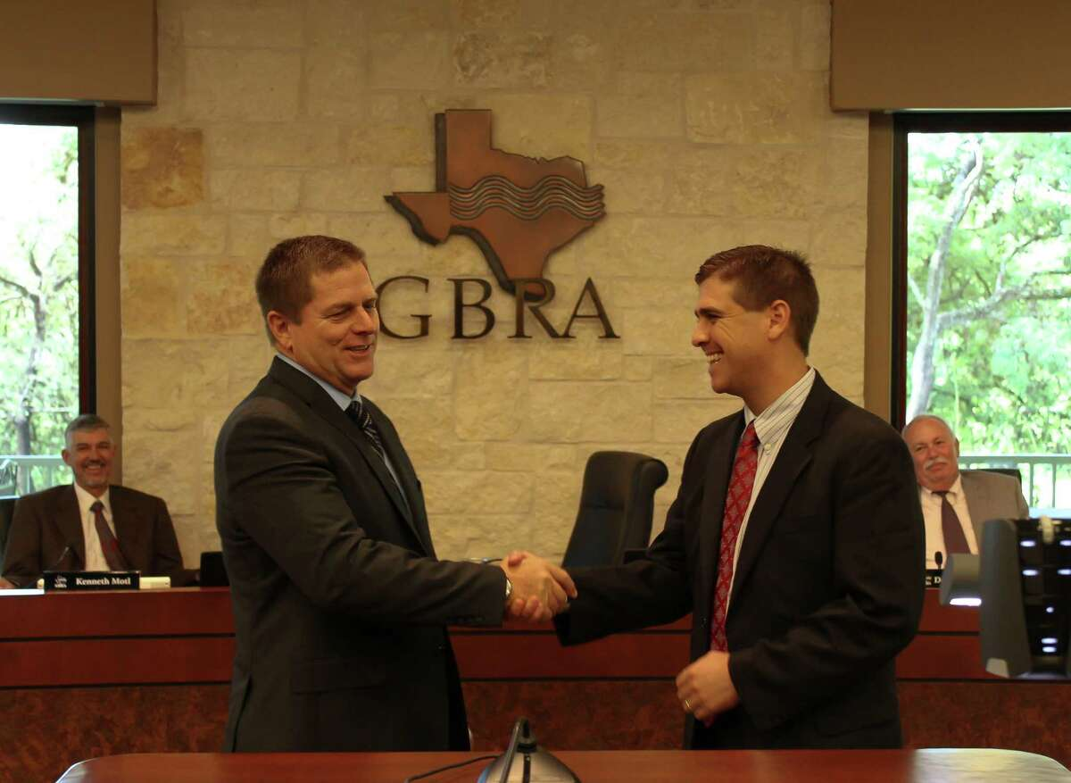Guadaluple-Blanco River Authority chairman Thomas Mathews, left, shakes hands with Kevin Patteson, the GBRA's new general manager. Patteson will take over from Bill West Jr., who has been with the agency for 22 years, on May 2.