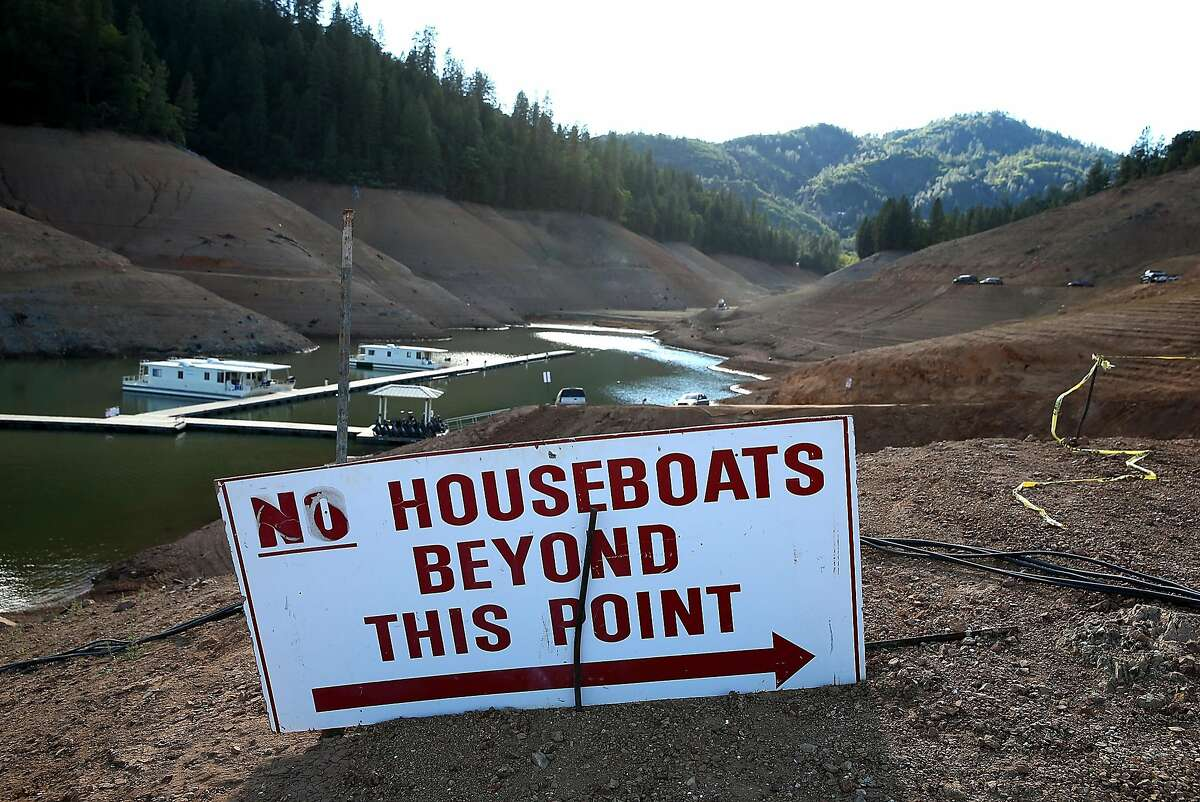 In this 2014 file photo, houseboats are dwarfed by the steep banks of Shasta Lake at Holiday Harbor during the drought.