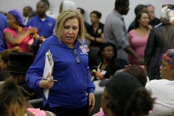 Maria Cisneros with the City of Houston Health and Human Services speaks with people during an informational meeting about the flood held at Harvest Time Church, 17770 Imperial Valley Dr., Wednesday, April 20, 2016, in Houston.