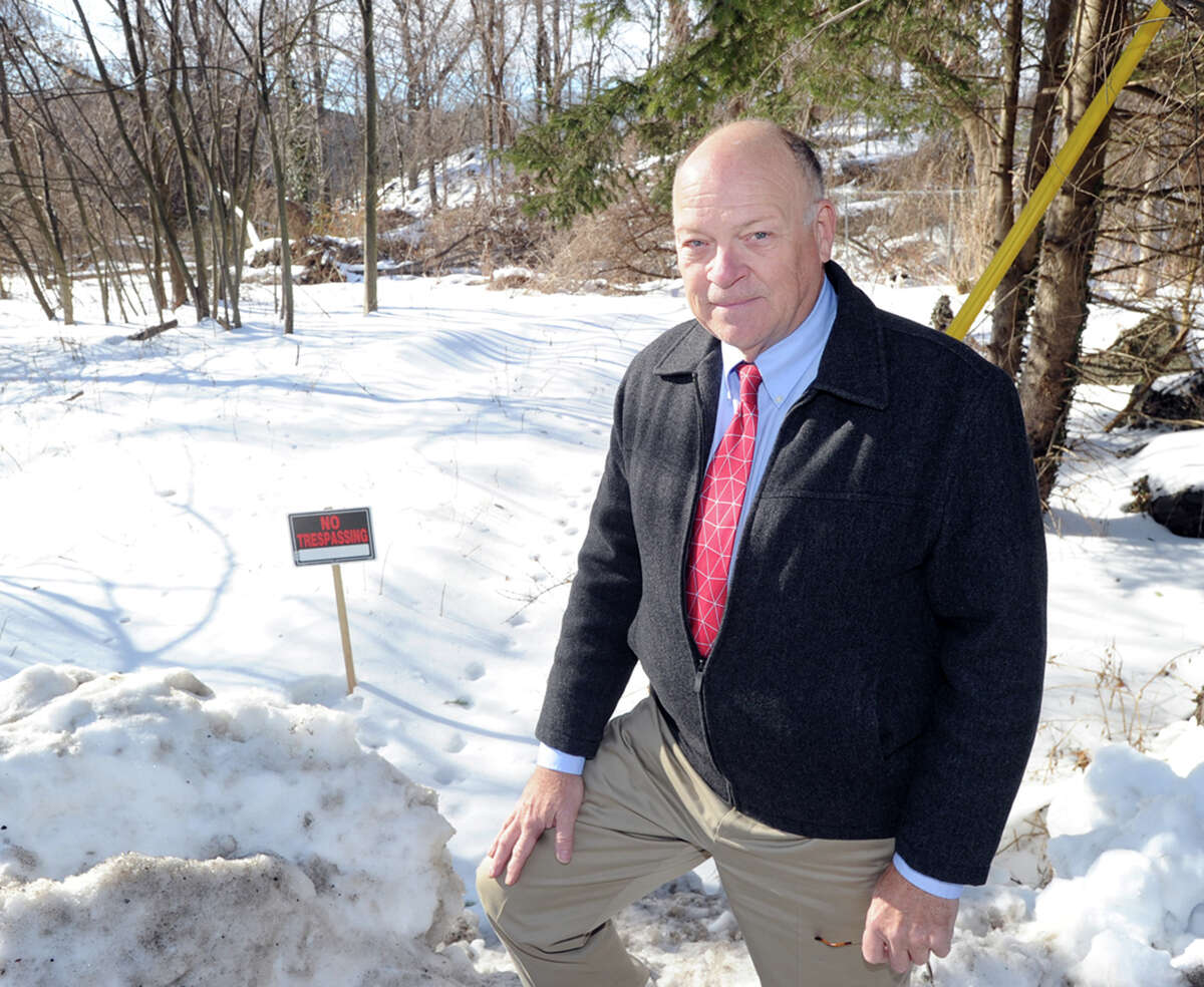 """Michael Finkbeiner, an environmental analyst, stands near a """"No Trespassing"""" sign staked in the Town of Greenwich owned Armstrong Court Housing complex property off Booth Place in the Chickahominy section of Greenwich, Conn., Wednesday, Feb. 11, 2015. According to a letter from Greenwich Housing officials, the town rescinded Finkbeiner's access to the property. Finkbeiner was in the prcoess of studying the soil on the property for toxicity for clients who live close to the site. This month, Finkbeiner conducted testing on the grounds of Western Middle School for neighbors."""