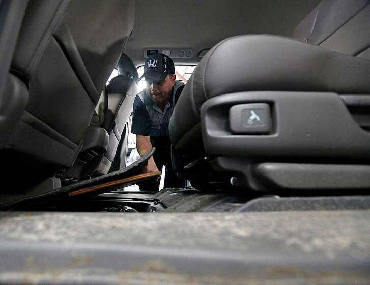 John Eagle Honda technician Shannon Smith checks  a spare tire panel in a Honda Odyssey for water.