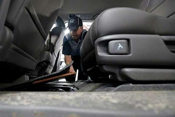 John Eagle Honda technician Shannon Smith checks  a spare tire panel in a Honda Odyssey for water.
