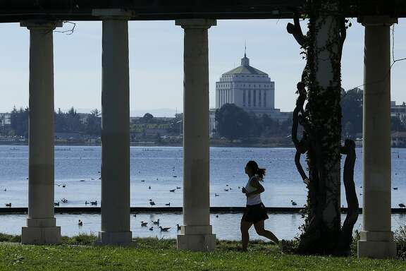 A woman jogs around Lake Merritt Tuesday, Feb. 16, 2016, in Oakland, Calif. Warm weather has returned to the Bay area before more rain is forecast later in the week. (AP Photo/Ben Margot)