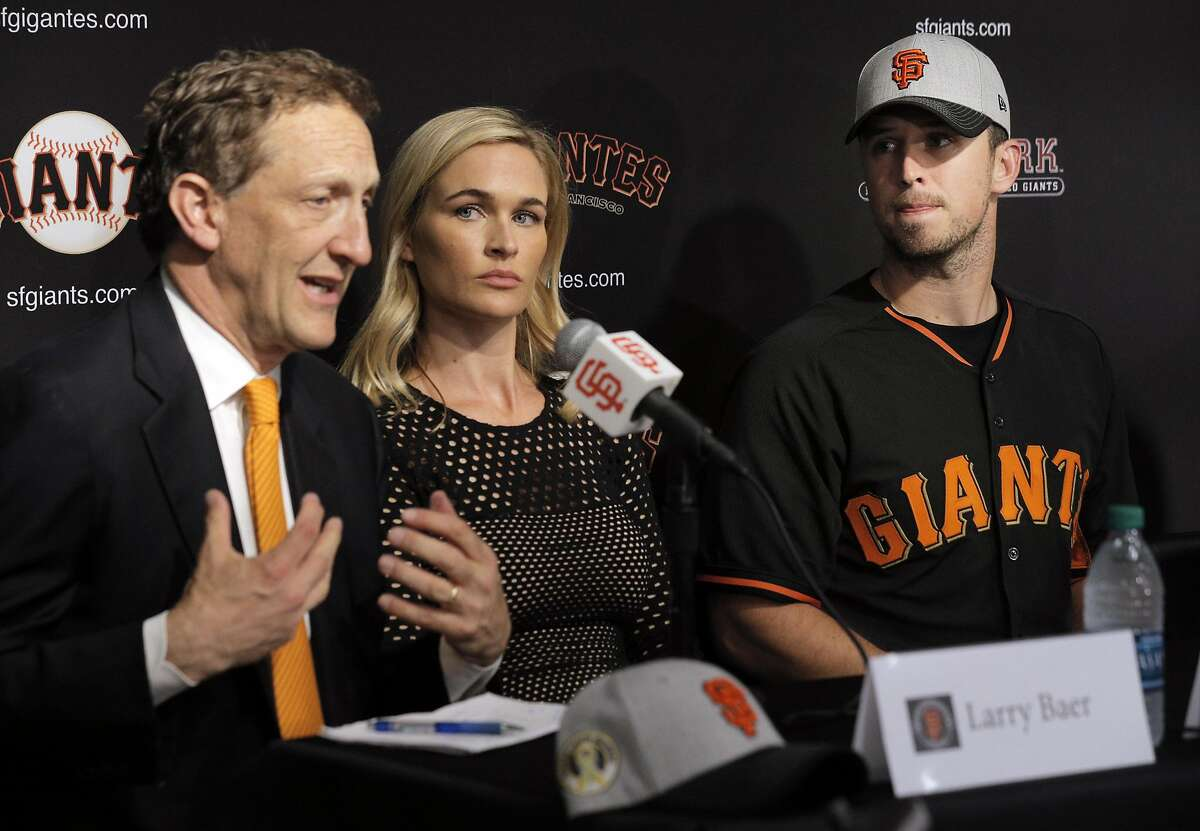 Kristen, center, and Buster Posey, right, listen as Larry Baer, left, speaks during a press conference at AT&T Park in San Francisco, Calif., on Wednesday, April 20, 2016. Buster and Kristen Posey, along with the San Francisco Giants, announced that they will be focusing their philanthropic efforts to the fight against pediatric cancer.