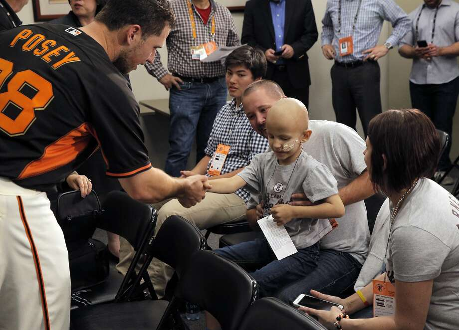 Buster Posey shakes hands with cancer patient Colby Arnett, 7, as he greets Colby and his parents Tim and Hillery after a press conference Wednesday. Photo: Carlos Avila Gonzalez, The Chronicle