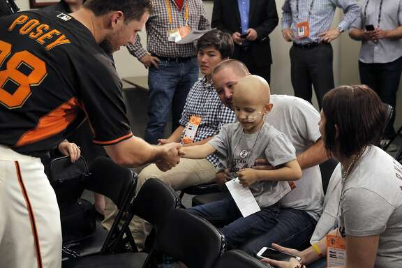 Buster Posey shakes hands with Colby Arnett, 7, as he greets Colby and his parents Tim and Hillery after a press conference at AT&T Park in San Francisco, Calif., on Wednesday, April 20, 2016.  Buster and Kristen Posey, along with the San Francisco Giants, announced that they will be focusing their philanthropic efforts to the fight against pediatric cancer.
