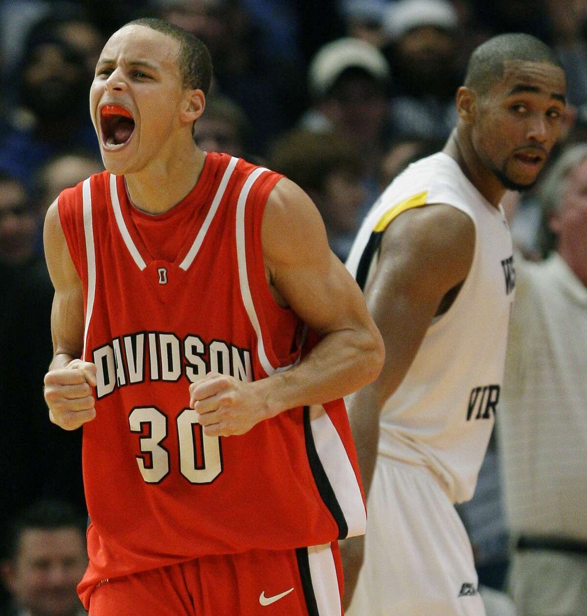 Davidson's Stephen Curry, left, reacts after a West Virginia turnover in the second half during a Jimmy V Classic NCAA college basketball game on Tuesday, Dec. 9, 2008, at Madison Square Garden in New York. Davidson won 68-65. West Virginia's Da'Sean Butler, right, looked on.(AP Photo/Julie Jacobson)