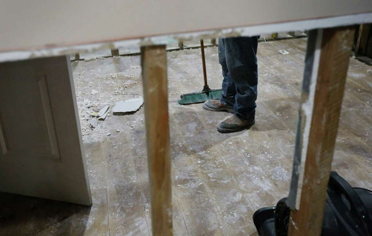 A contractor works in the home of Tom Harari, in the Meyerland area, Wednesday, April 20, 2016, in Houston. Harari and his family have been through multiple floods, and he says they are afraid of losing the sense of community as neighbors decide to move away.