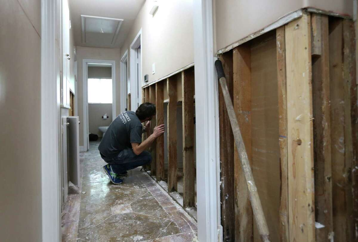 Tom Harari looks through the wall into one of the bedrooms in his Meyerland home, Wednesday, April 20, 2016, in Houston. Harari and his family have been through multiple floods, and he says they are afraid of losing the sense of community as neighbors decide to move away.