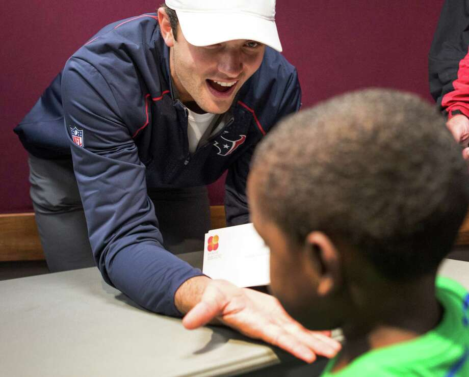 Quarterback Brock Osweiler greets a youngster during a visit Wednesday by several Texans players to the shelter for flood victims at the Campbell Center. The players handed out gift cards, served pizza and tried to act as morale boosters. Story on page A2. Photo: Brett Coomer, Staff / © 2016 Houston Chronicle