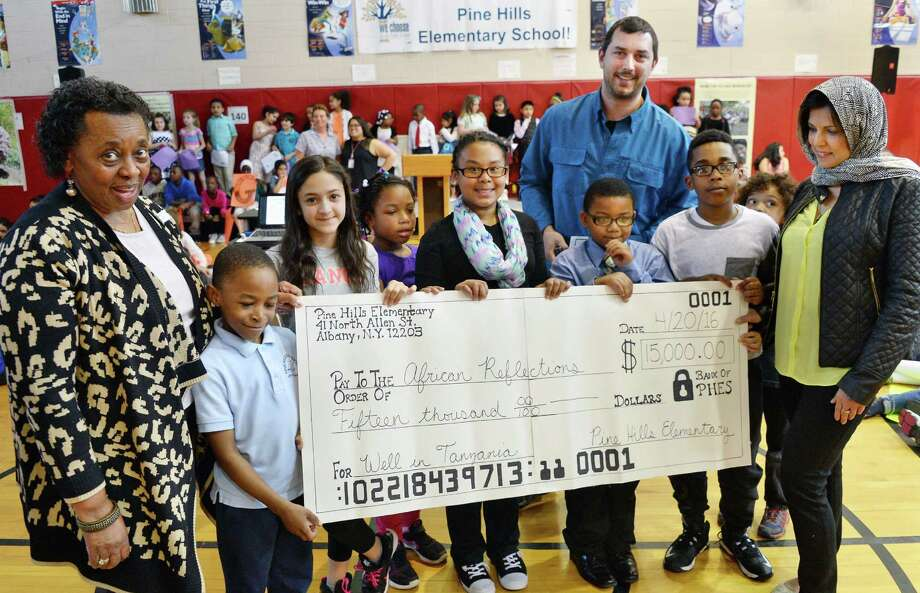 Jean Dobbs of African Reflections Foundation, left, Kevin Bailey,owner of High Peaks Solarand and African Reflections Foundation president Sajida Mamdani, right, receive a check from the students at Pine Hills Elementary who raised $15,000 to support a deep water well in rural Tanzania during a ceremony at the school Wednesday April 20, 2016 in Albany, NY.  (John Carl D'Annibale / Times Union) Photo: John Carl D'Annibale / 10036266A