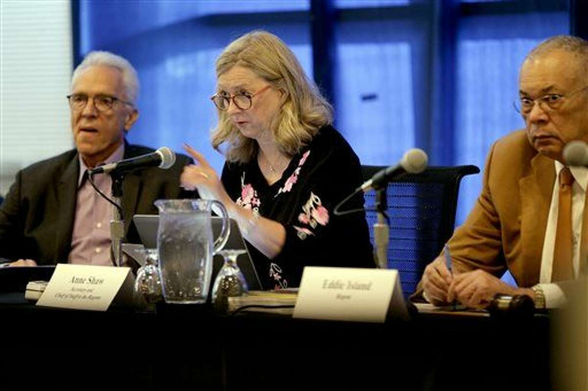 FILE- In this Oct. 26, 2015, file photo, University of California regents Norman Pattiz, left, and Eddie Island, right, flank board secretary and chief of staff Anne Shawn during a public forum on how best to deal with intolerance at the university, on the campus at UCLA in Los Angeles.