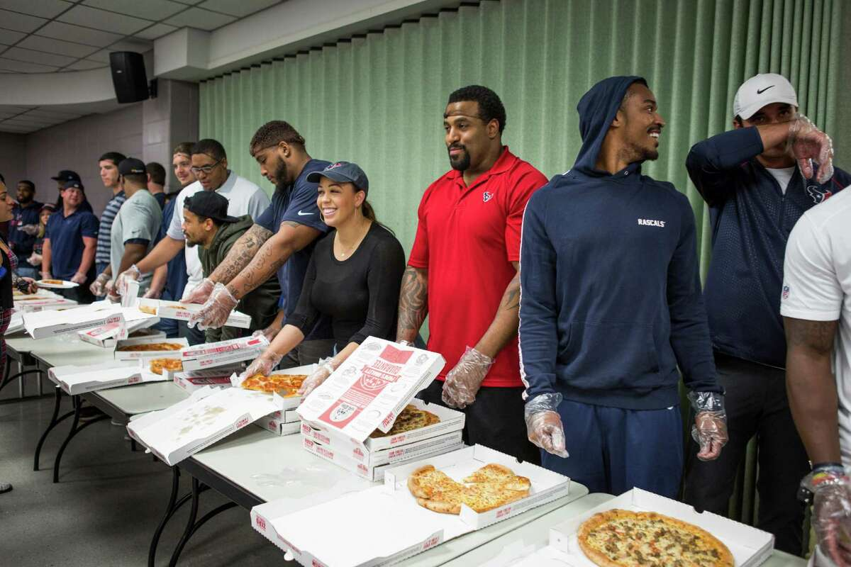 A group of Houston Texans players line uip to serve pizza to flood victims living in the shelter at the M.O. Campbell Center on Wednesday, April 20, 2016, in Houston. The players handed out gift cards, pillows and served pizza.