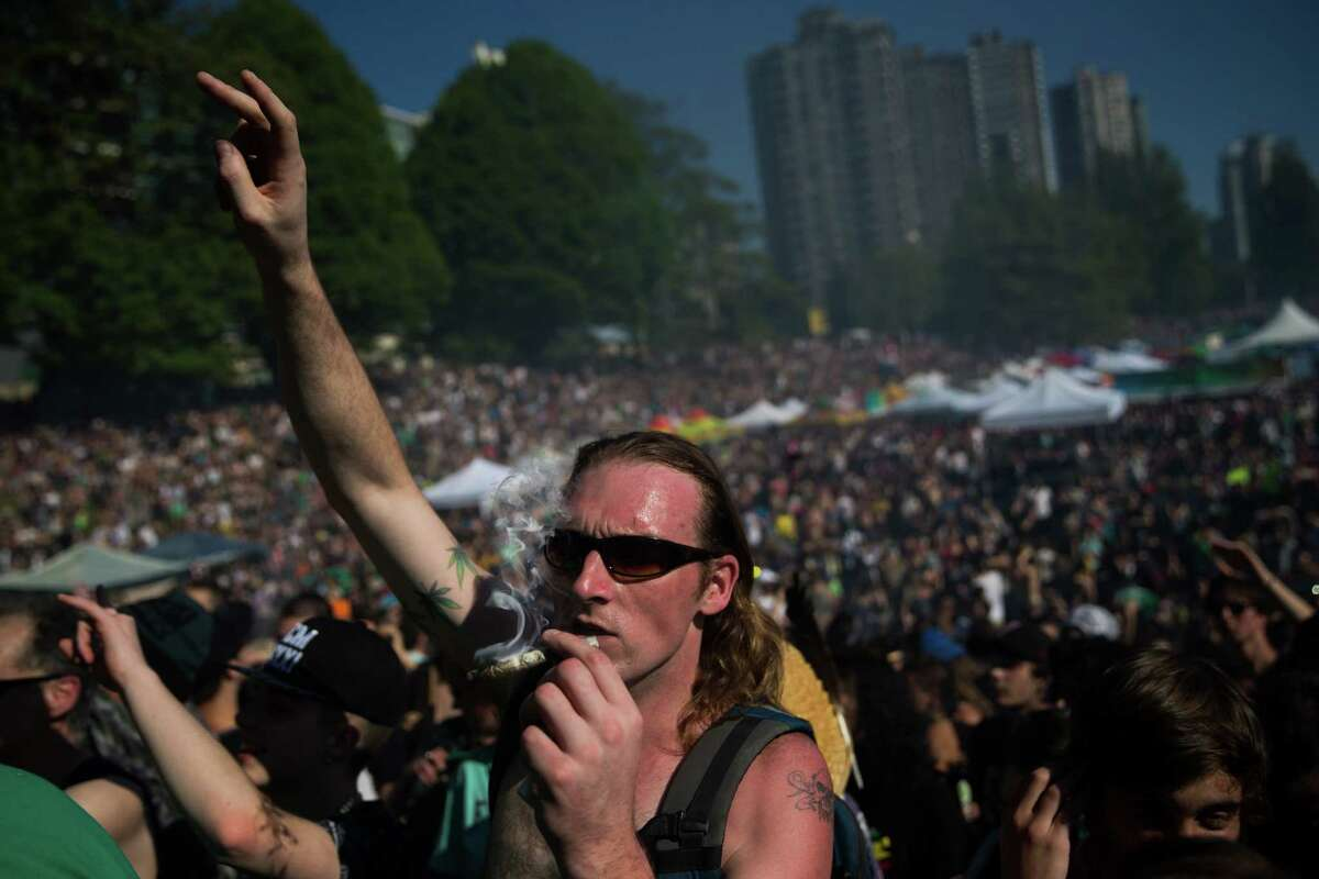A man smokes as the clock hits 4:20 p.m. at 420 Vancouver at Sunset Beach in Vancouver, B.C. on Wednesday, April 20, 2016.