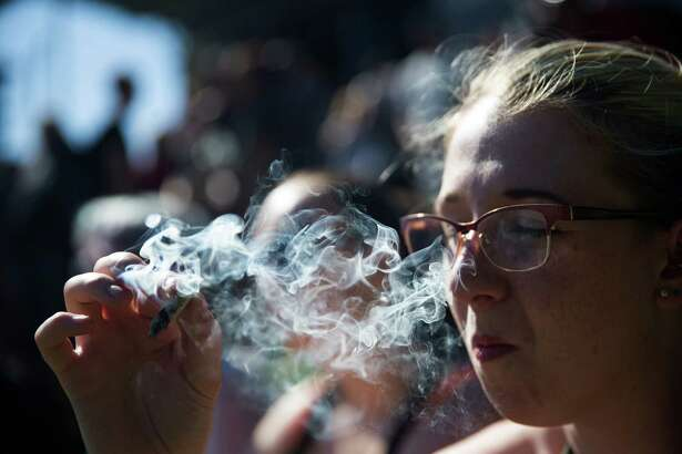 Rachel McGilliwray holds a joint at 420 Vancouver at Sunset Beach in Vancouver, B.C. on Wednesday, April 20, 2016.