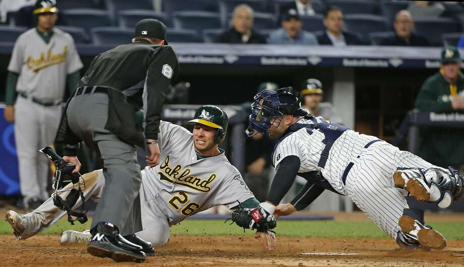 Home plate umpire Jeff Kellogg (8) watches as Oakland Athletics' Danny Valencia (26) is tagged out at the plate by New York Yankees catcher Brian McCann (34) on Yonder Alsonso's fourth-inning fly-out in a baseball game in New York, Wednesday, April 20, 2016. (AP Photo/Kathy Willens) Photo: Kathy Willens, Associated Press