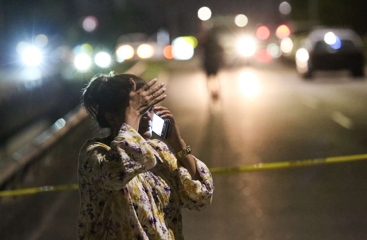 A woman talks on the phone at the scene where a body was discovered in Sims Bayou in southeast Houston on Wednesday night.