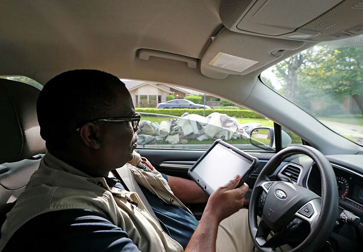 """Melvin Hopkins, a code enforcement officer with the City of Houston's Department of Neighborhoods, surveys residential damage on Wednesday in the Meyerland area. """"We have a lot of ground to cover,"""" Hopkins said. """"Basically, all four corners of the city."""""""