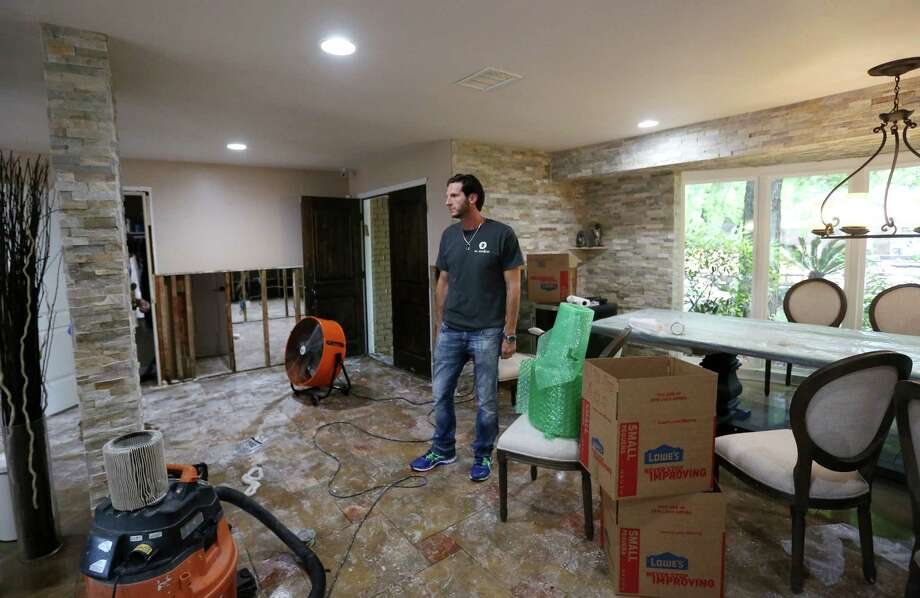 Tom Harari pauses Wednesday to look the few remaining items in his Meyerland home. Harari said his family has been through multiple floods and now fears losing the sense of community if neighbors decide to move away. Photo: Jon Shapley, Staff / © 2015  Houston Chronicle
