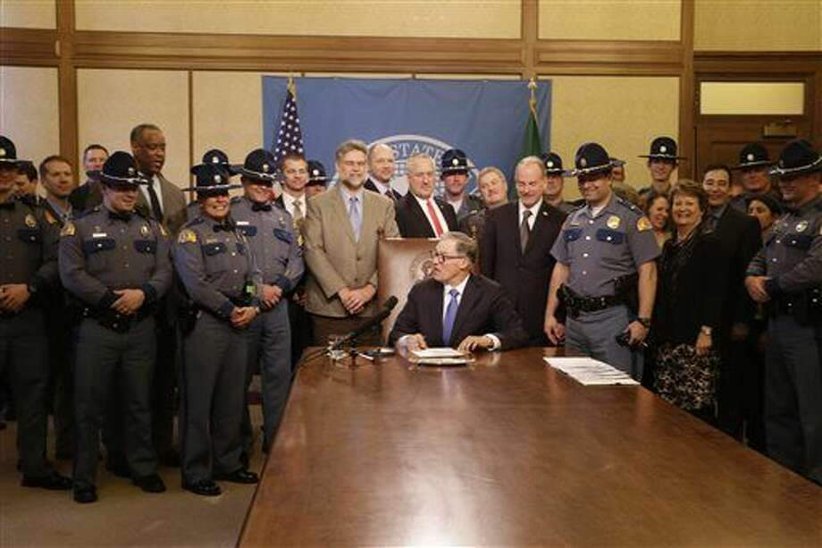 Washington Gov. Jay Inslee, seated, prepares to pose for a photo with Washington State Patrol troopers after signing a bill that boosts their pay, Friday, March 25, 2016, in Olympia, Wash. The state transportation budget sets aside $5 million for a 5 percent salary increase for patrol officers starting in July. (AP Photo/Rachel La Corte) Photo: Rachel La Corte