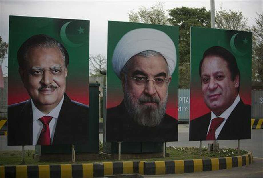 The hoardings of visiting Iranian President Hassan Rouhani, center, is on display with Pakistan's Prime Minister Nawaz Sharif, right, and President Mamnoon Hussain at the Constitution Avenue in Islamabad, Pakistan, Friday, March 25, 2016. Rouhani was expected in Pakistan on Friday in a landmark visit, his first since becoming president, at a time when Saudi Arabia is courting Islamabad to increase participation in a new Saudi-led military alliance of mostly Sunni nations, a coalition perceived by Tehran as an anti-Shiite block. (AP Photo/B.K. Bangash) Photo: B.K. Bangash
