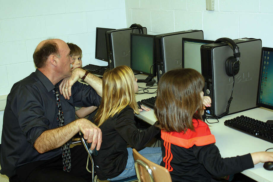 Fourth grade Deckerville teacher Gary Cesefske assists students with math problems on the school's computers after school. It is a special program created by national firm, TenMarks, for the month of March. It is called Math Madness. Here, he helps (from left) Zane Sargent, Johanna Kubacki and Lola Fortushniak.