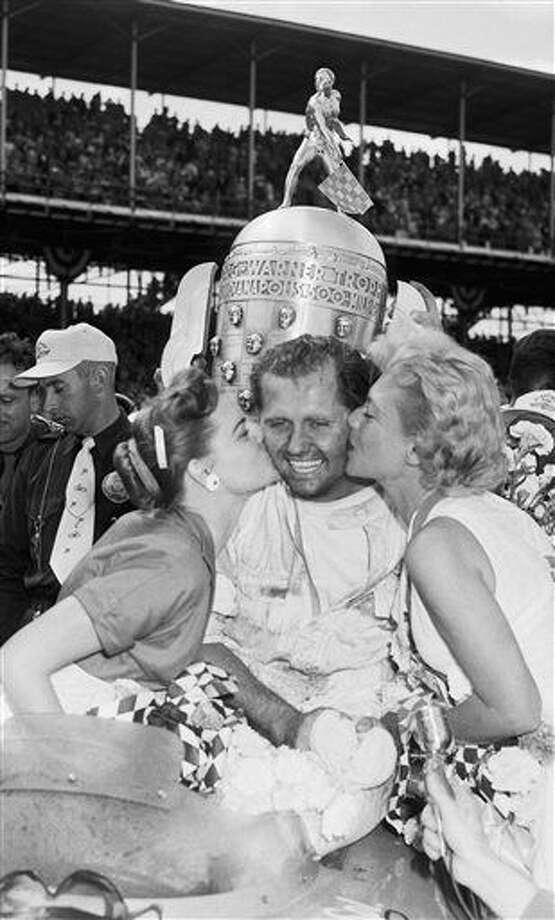 FILE - In this May 30, 1955, file photo, Bob Sweikert receives kisses from his wife, Dolores, left, and singer Dinah Shore after winning the 39th Indianapolis 500 auto race at Indianapolis Motor Speedway in Indianapolis, Ind. (AP Photo/File) Photo: Anonymous