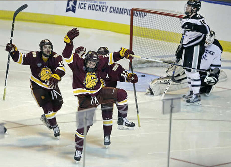 Minnesota-Duluth wing Karson Kuhlman (20) celebrates his winning goal with teammates Willie Raskob, left, and Austin Farley, right, as Providence defenseman Anthony Florentino (16) and goalie Nick Ellis (35) react in the second overtime period of a regional semifinal game in the NCAA college hockey tournament, Friday, March 25, 2016, in Worcester, Mass. Minnesota-Duluth won 2-1. (AP Photo/Elise Amendola) Photo: Elise Amendola