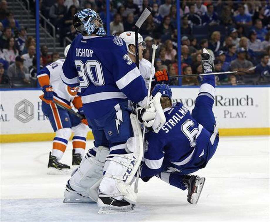 Tampa Bay Lightning's Anton Stralman, of Sweden, falls in front of goalie Ben Bishop during the first period of an NHL hockey game against the New York Islanders on Friday, March 25, 2016, in Tampa, Fla. Stralman was helped off the ice and did not immediately return. (AP Photo/Mike Carlson) Photo: Mike Carlson
