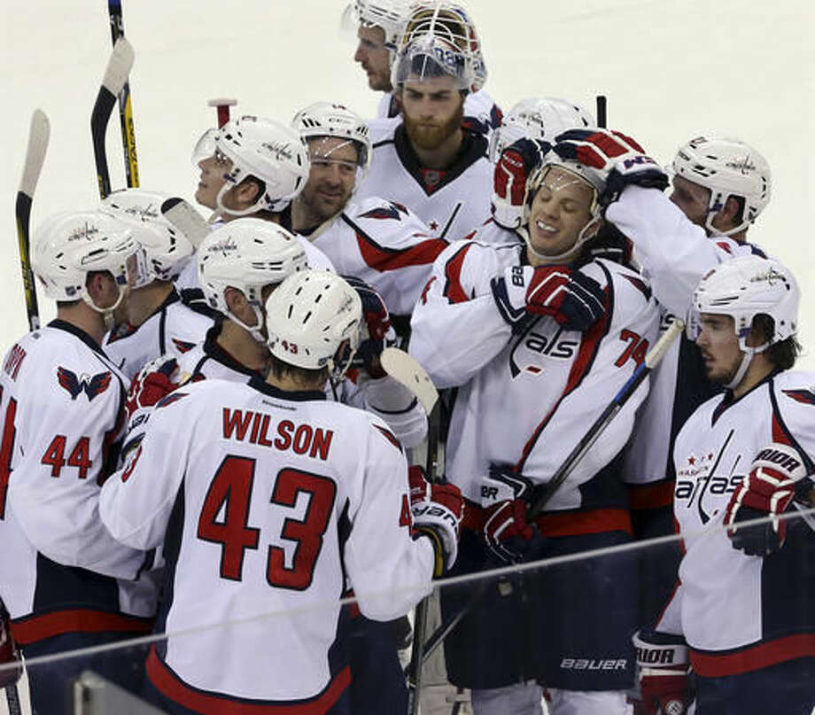 Washington Capitals players gather around defenseman John Carlson (74) as they celebrate his winning goal in overtime during an NHL hockey game against the New Jersey Devils Friday, March 25, 2016, in Newark, N.J. (AP Photo/Mel Evans) Photo: Mel Evans