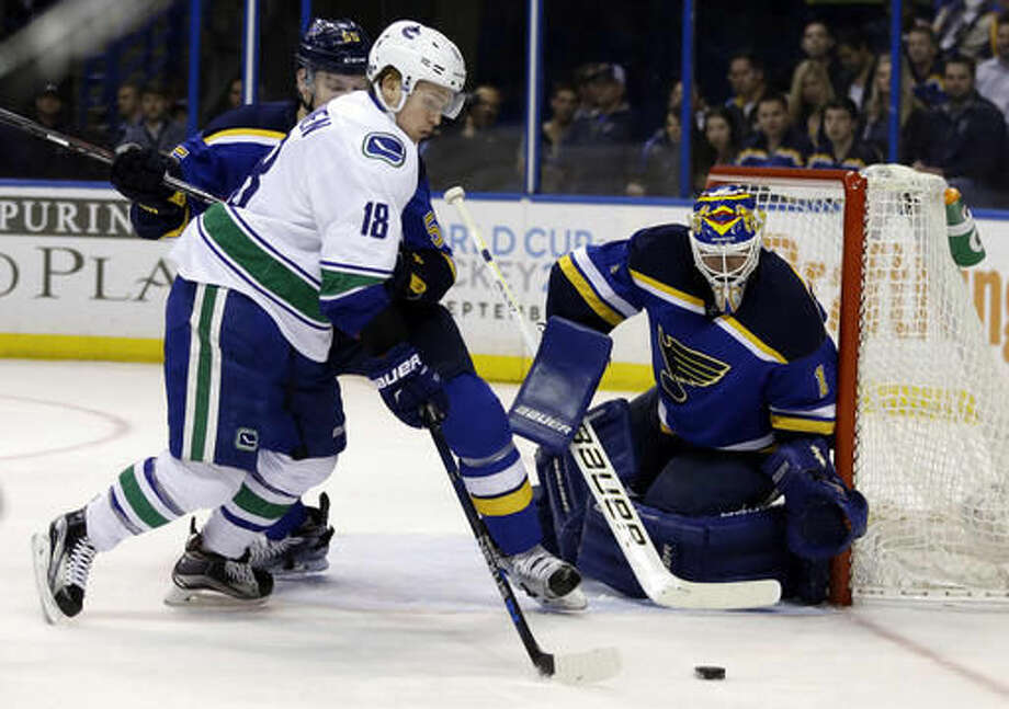 Vancouver Canucks' Jake Virtanen, left, controls the puck as St. Louis Blues goalie Brian Elliott defends during the first period of an NHL hockey game Friday, March 25, 2016, in St. Louis. (AP Photo/Jeff Roberson) Photo: Jeff Roberson