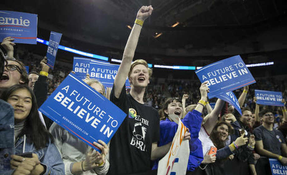 FILE - In this March 20, 2016 file photo, supporters of Democratic presidential candidate Sen. Bernie Sanders, I-Vt., cheer at a campaign rally by Sanders in Seattle. Sanders' brand of democratic socialism may take some explaining in some parts of the United States, but not in Seattle. This city elected a socialist to the City Council in 2013 and was among the first to phase in a $15 an hour minimum wage, mandate sick leave for most companies and offer paid parental leave for city workers - issues that mirror Sanders' platform. (AP Photo/Stephen Brashear, File) Photo: Stephen Brashear