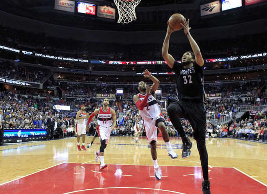 Minnesota Timberwolves center Karl-Anthony Towns (32) shoots in front of Washington Wizards guard John Wall (2) late in the second overtime period of an NBA basketball game Friday, March 25, 2016, in Washington. The Timberwolves won 132-129. (AP Photo/Alex Brandon) Photo: Alex Brandon