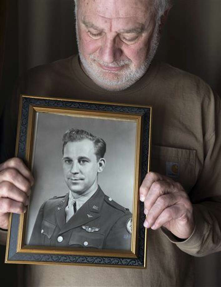 ADVANCE FOR WEEKEND EDITIONS MARCH 26-27 - In this March 17, 2016 photo, Al Paffenroth Jr. poses in his home with a photograph of his father Al Paffenroth, Sr.in Tacoma, Wash. Paffenroth still hopes that the remains of his father, Al Sr. will one day be recovered. His plane went missing somewhere near Pyongyang in the early stages of the Korean War. (Drew Perine/The News Tribune via AP) MANDATORY CREDIT Photo: Drew Perine