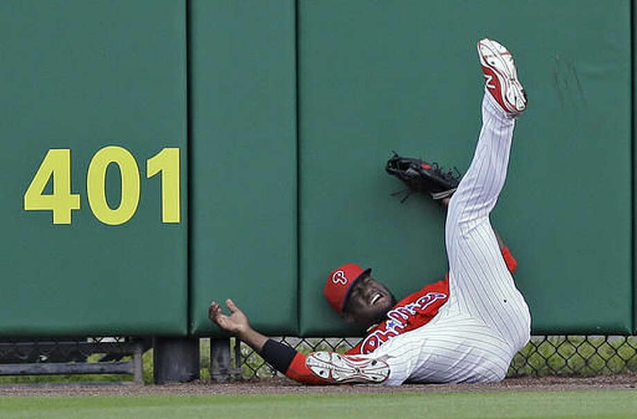 Philadelphia Phillies center fielder Odubel Herrera crashes into the wall chasing down a fly out by Toronto Blue Jays' Kevin Pillar during the first inning of a spring training baseball game Friday, March 25, 2016, in Clearwater, Fla. (AP Photo/Chris O'Meara) Photo: Chris O'Meara
