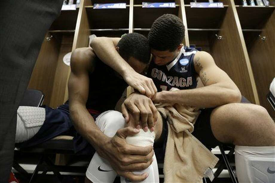 Gonzaga's Eric McClellan (23) and Josh Perkins (13) embrace in the locker room after an NCAA college basketball game in the regional semifinals of the NCAA Tournament, Friday, March 25, 2016, in Chicago. Syracuse won 63-60. (AP Photo/Nam Y. Huh) Photo: Nam Y. Huh