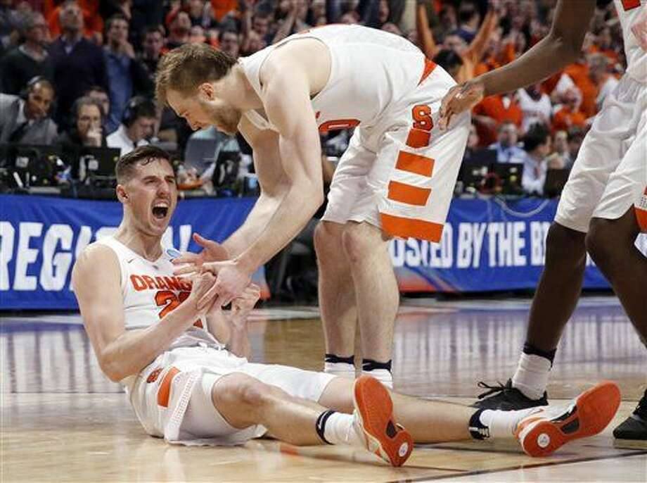Syracuse's Tyler Lydon (20) celebrates with Trevor Cooney (10) after getting fouled in the final seconds of a college basketball game in the regional semifinals of the NCAA Tournament, Friday, March 25, 2016, in Chicago. Syracuse won 63-60. (AP Photo/Charles Rex Arbogast) Photo: Charles Rex Arbogast
