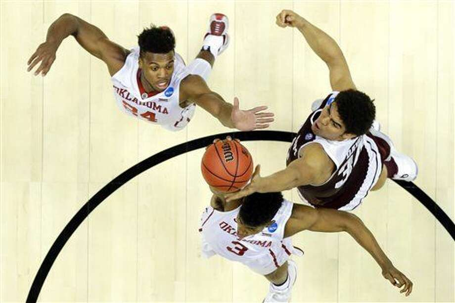 Texas A&M center Tyler Davis, right, pulls a rebound away from Oklahoma guard Christian James, bottom, and Buddy Hield during the first half of an NCAA college basketball game in the regional semifinals of the NCAA Tournament, Thursday, March 24, 2016, in Anaheim, Calif. (AP Photo/Gregory Bull) Photo: Gregory Bull
