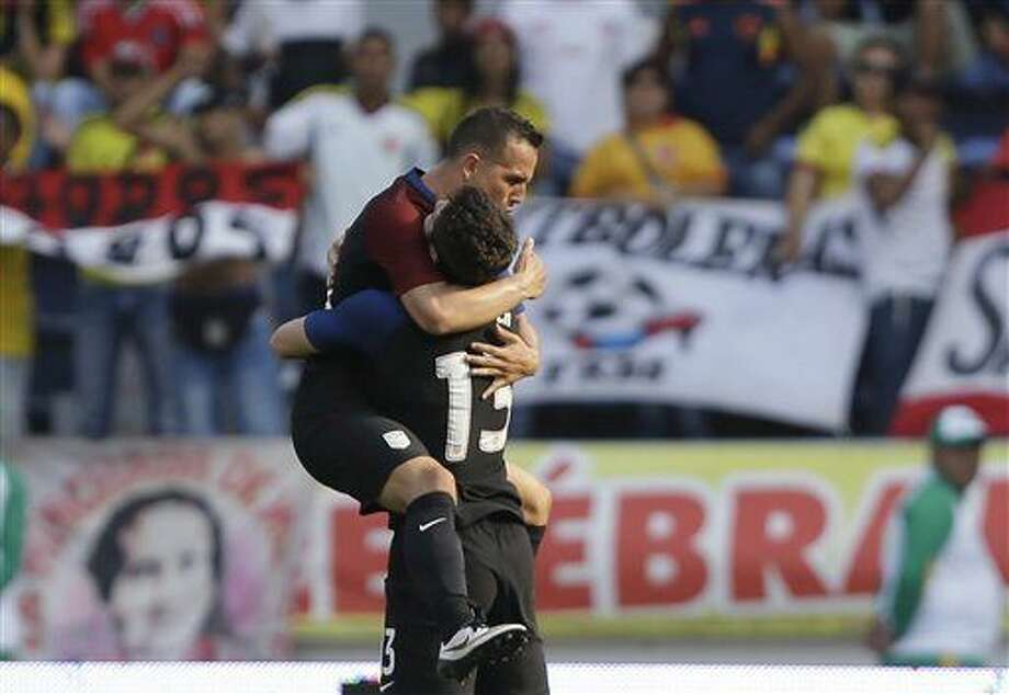 United States' Luis Gil, left, is embraced by teammate Matt Polster after scoring his side's first goal against Colombia during a U-23 first leg soccer match qualifier for the 2016 Rio Olympics at the Roberto Melendez Stadium in Barranquilla, Colombia, Friday, March 25, 2016. (AP Photo/Fernando Vergara) Photo: Fernando Vergara