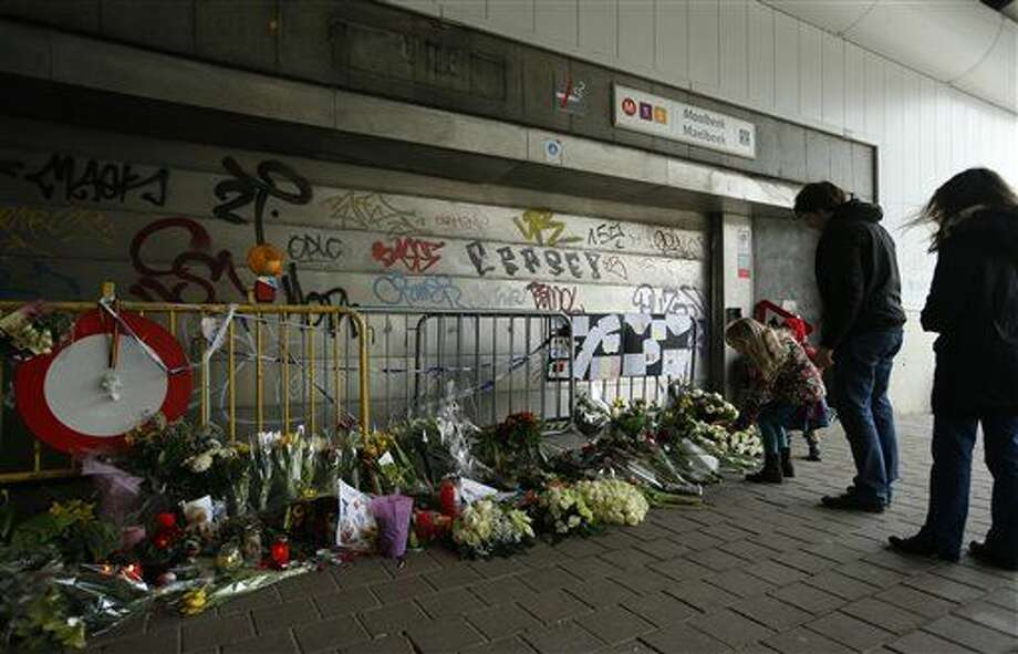 People stop and look at floral tributes placed outside the Maelbeek metro station, the scene of one of the bomb attacks on the Belgian capital, in Brussels, Saturday, March 26, 2016. Brussels airport officials say flights won't resume before Tuesday as they assess the damage caused by twin explosions in the terminal earlier this week. (AP Photo/Alastair Grant) Photo: Alastair Grant