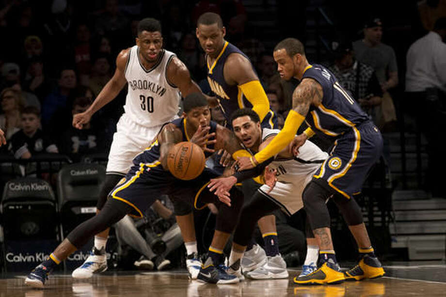 Indiana Pacers forward Paul George, front left, and Brooklyn Nets guard Shane Larkin, front right, fight for the ball during the first half of an NBA basketball game, Saturday, March 26, 2016, at New York. (AP Photo/Mary Altaffer) Photo: Mary Altaffer