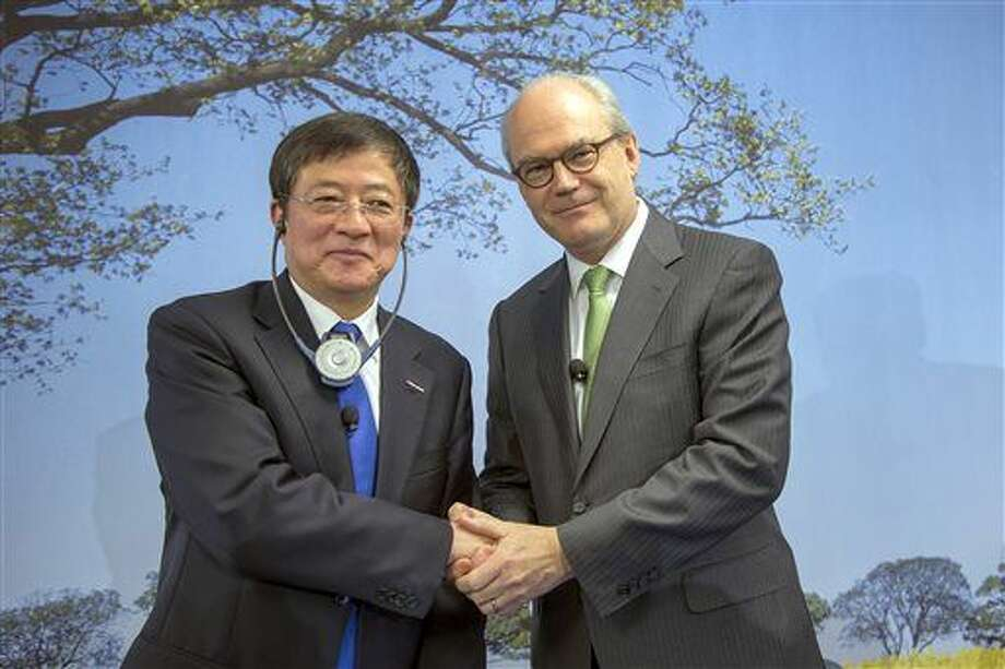 FILE - In this Feb. 3, 2016, file photo, Ren Jianxin, left, chairman of ChemChina (China National Chemical Corporation), and Michel Demare, chairman of the Board of Directors of Syngenta, pose for a photo after an annual press conference of agrochemical company Syngenta in Basel, Switzerland. The tycoon who is offering $43 billion for Swiss agrochemicals giant Syngenta keeps a low profile but is China's most aggressive dealmaker. (Georgios Kefalas/Keystone via AP, File) Photo: Georgios Kefalas
