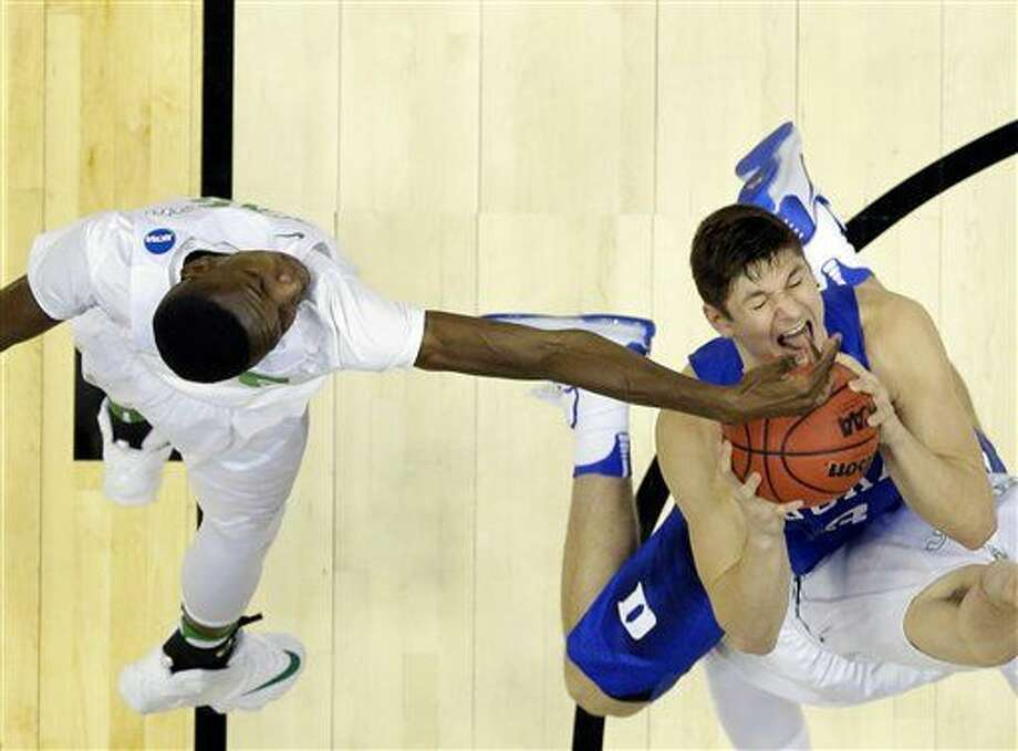 Oregon forward Chris Boucher, left, fouls Duke guard Grayson Allen during the second half of an NCAA college basketball game in the regional semifinals of the NCAA Tournament, Thursday, March 24, 2016, in Anaheim, Calif. (AP Photo/Gregory Bull) Photo: Gregory Bull